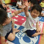 手を挙げて、お誕生日のお友達に質問しようとしています。